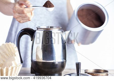 A Caucasian Woman Is Taking A Teaspoon Of Ground Coffee From A Jar Using A Plastic Measuring Spoon A