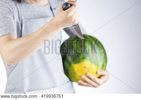 A Caucasian Woman Is Preparing To Stab A Watermelon Using A Sharp Kitchen Knife. A Versatile Image F