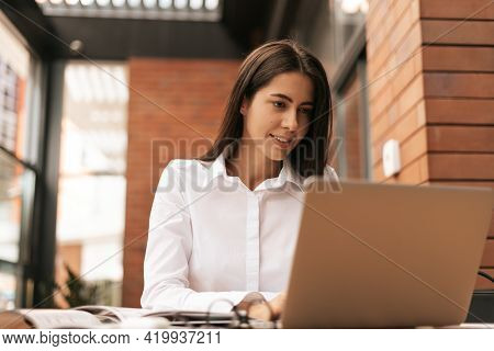 Concentrated At Work. Young Beautiful Woman Using Her Laptop While Sitting. Beautiful Clever Cute Ch