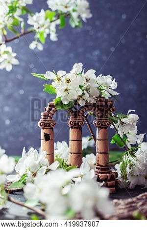 Small Ruins With Columns In White Flowers. Blooming Apple Tree Branches Next To The Greek Columns