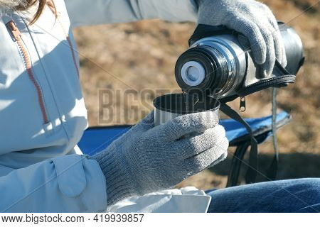 Closeup Hands Of Woman In Gloves Pouring Hot Tea From Thermos Bottle On Nature. Food And Drink On Na