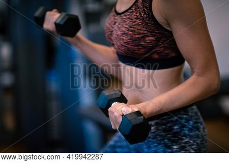 Girl with Dumbbells is Engaged in the Gym. Reduces Weight. Body Care. Body Building. Strong Muscles. Healthy Sports Lifestyle.