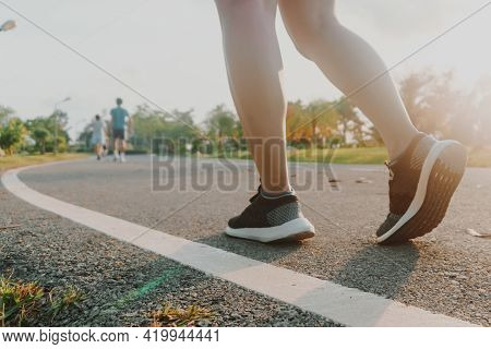 Woman Wear Running Shoe On To Walking And Running On Nature Green Background.health Exercise.