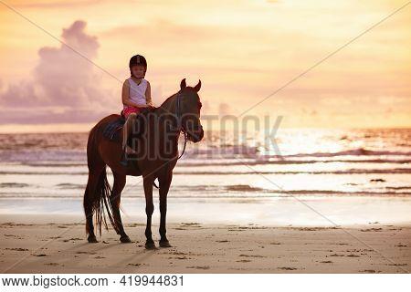 Kids Riding Horse On Beach. Children Ride Horses.