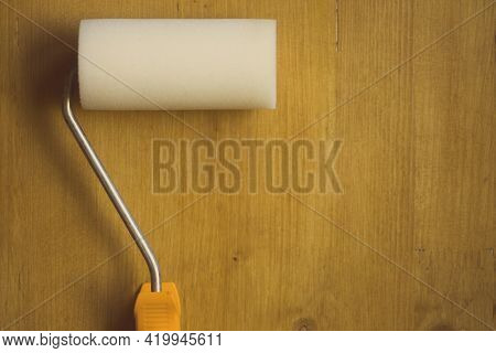 Paint Roller On A Wooden Background