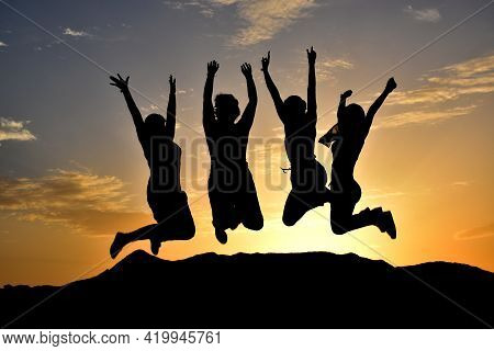 Silhouette Of Happy Group Of Girls Jumping At Sunset. Concept Of Friendship Or Freedom. Unrecognizab