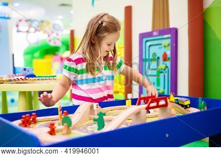 Kids Play Toy Railroad. Little Girl With Wooden Trains In Indoor Playground Or Amusement Center. Chi