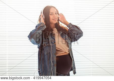 Beautiful Young Peaceful Pregnant Woman Listens To Pleasant Classical Music Using Smartphone And Hea
