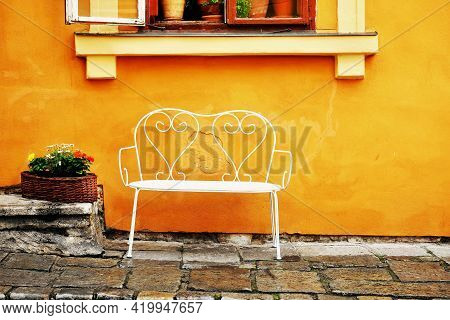 Street Photo. White Bench Under House Window. There Are Flowers In The Window And On The Street. The