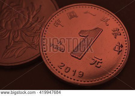 1 One Chinese Yuan Coins Close-up. Dark Red Tinted Background Or Wallpaper. Economy, Business, Money