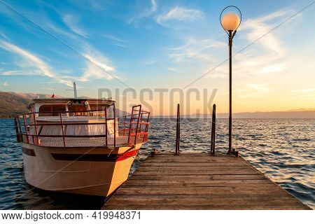 Beautiful Sky Of The Setting Sun On Lake Ohrid With A View From The Pier With A Moored Boat.