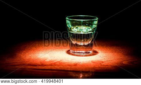 A Shot With Alcohol On A Wooden Bar. Illuminated Glass With Alcohol On The Bar Counter.