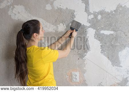 A Woman Repairman Puts A Putty On The Wall. Smearing The Roughness. Repair With Your Own Hands. Plac