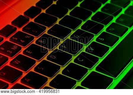 Close Up View Of A Computer Keyboard Keys In Red And Green Tones. Modern Computer Wireless Keyboard