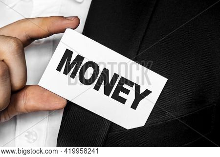Inscription Money On A White Business Card. A Man In A Black Business Suit Lowers Or Removes From Hi