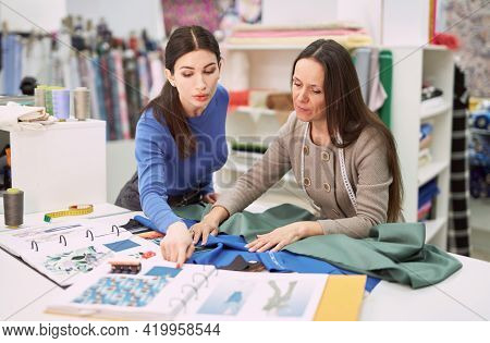 Attractive Female Consultant In Textile Store Demonstrating Linen Fabrics To Young Brunette Tailor O