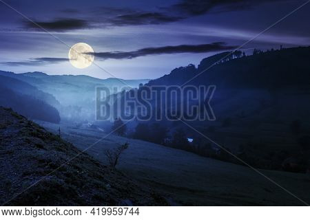 Valley On The Foggy Night. Village In The Distance. Grass And Flowers On The Hill In Full Moon Light
