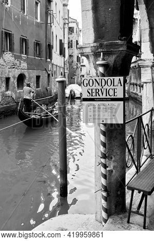 Venice, Italy  - June 18, 2018: Gondola service sign by canal in Venice. Black and white photography