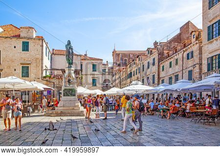 Dubrovnik, Croatia - Jine 12, 2017: Old square with walking people in Dubrovnik. Cityscape