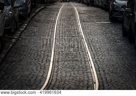 Close Up On A Tramway Rail Track On A Cobblestone Pavement On An Old And Obsolete Street Where Publi