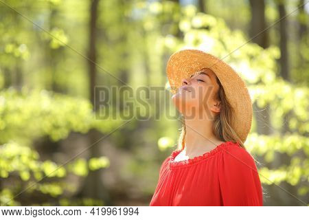 Happy Woman In Red Wearing Pamela Breathing Fresh Air In A Green Forest