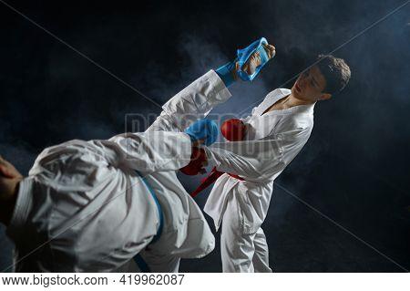 Two male karatekas in white kimono and gloves