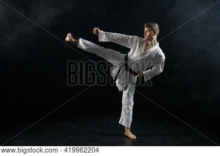 Male karateka, fighter in black kimono, training