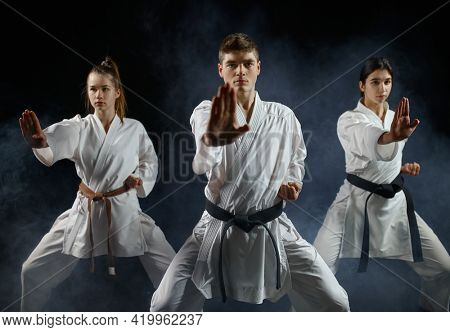 Female karate fighters, training with master
