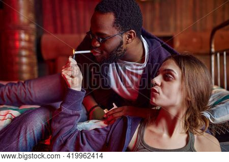 Drug addicts smokes a cigarette while high in den
