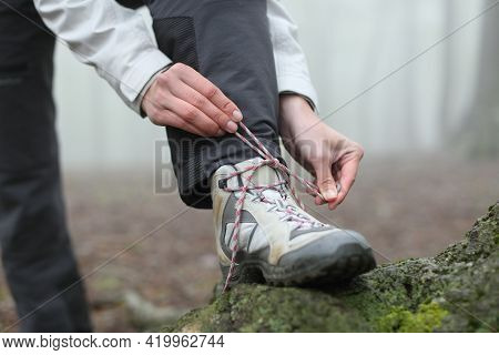 Close Up Of A Hiker Hands Tying Boot Laces In The Mountain