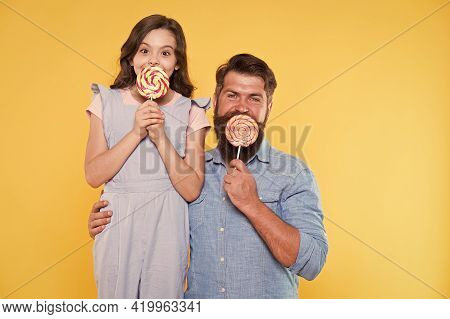 Sweet Life. How To Please Your Child And Avoid Problems. Sweet Food. Girl Child And Dad Hold Lollipo