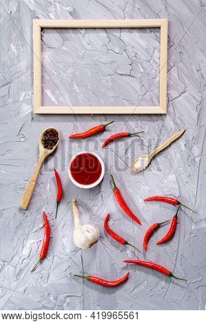 Composition With Chilli Pepper Sauce, Garlic And Sauce On Gray Background. Top View Copy Space