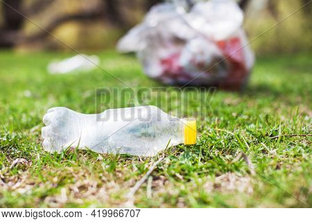 Empty plastic bottle on the grass in the park. Global problem of environmental pollution