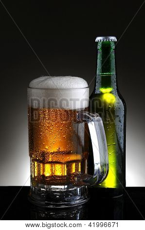 Closeup of a cold mug of beer and bottle on a light to dark gray background.