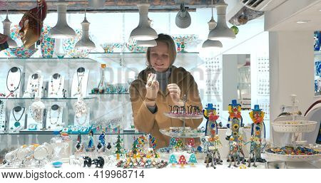 Woman Tourist Choosing Souvenirs In Venetian Shop