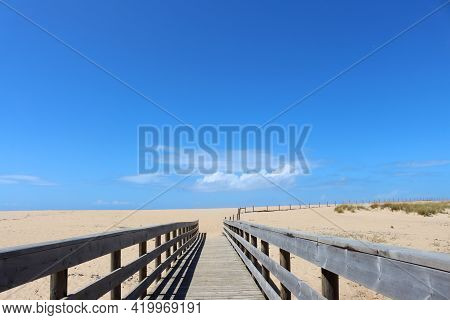 Long  Wooden Bridge Leading To The Sandy Beach And The Atlantic Ocean. Portugal Beaches.