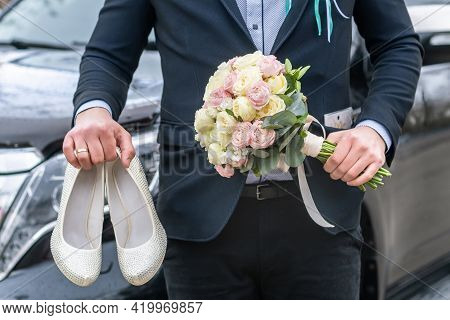 Groom Dressed In Blue Suit Holding A Bridal Bouquet Of Roses And White Female Wedding Shoes On A Car