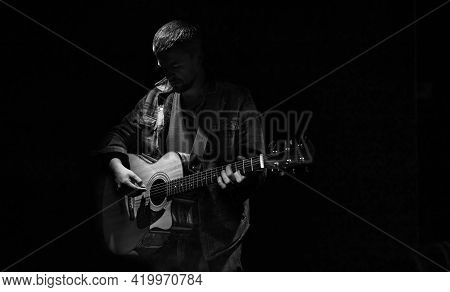 Male Guitarist Playing Acoustic Guitar In Dark Room.