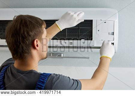 Portrait Of A Male Technician In White Gloves Repairing An Air Conditioner With A Screwdriver. Maint