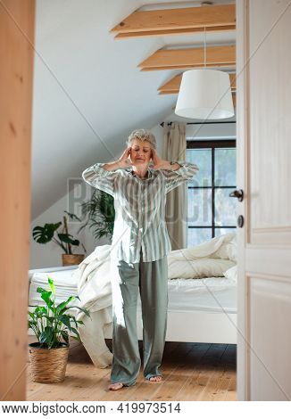 Senior Woman In Bed At Home Getting Up In The Morning, Stretching.