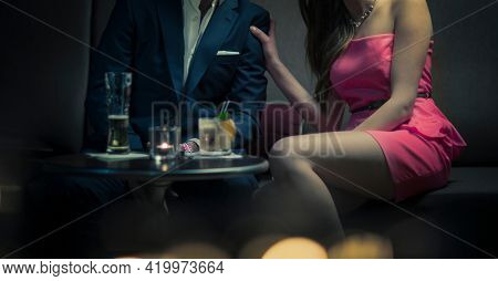 A woman and man flirting with drinks at a bar