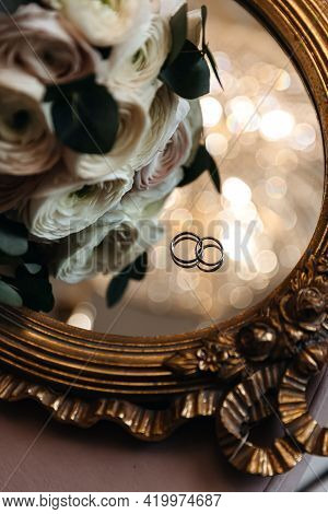 Wedding Rings Of The Bride And Groom On A Mirror Surface With Boke Near Fresh Flowers. Celebration O