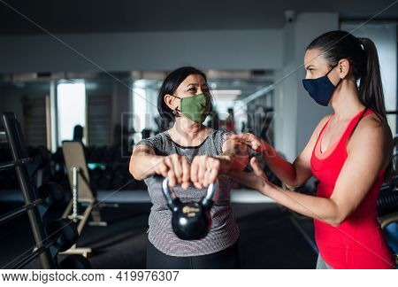 Senior Woman With Personal Trainer Doing Exercise In Gym, Coronavirus Concept.