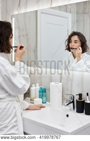 Woman In White Bathrobes Brushing Teeth In Front Of Mirror