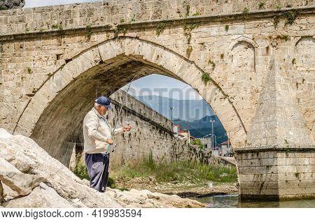 Visegrad, Bosnia, August 16, -  Bosnia And Herzegovina, 2014: Fisherman At Mehmed Pasa Sokolovic Bri