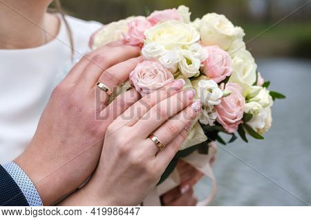 Bride And Groom Holding Bridal Bouquet Of Roses Together. Wedding Rings Are On A Fingers.