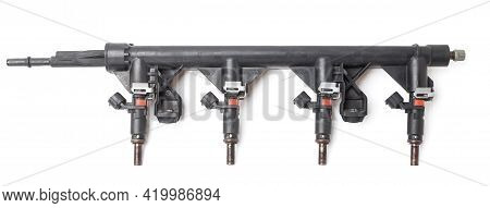 Close-up On A Car Fuel Rail With Injectors For Supplying Gasoline To A Four Cylinder Engine On A Whi