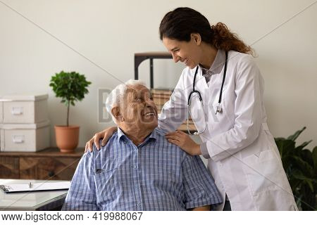 Optimistic Female Doc Embrace Shoulders Of Laughing Old Man Patient