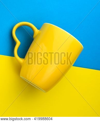 Empty Yellow Mug For Coffee And Tea On Yellow And Blue Background. The Colors Of The Swedish Nationa