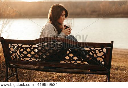 Side View Of Tranquil Female Sitting On Bench On Shore Of Lake And Warming With Paper Cup Of Coffee